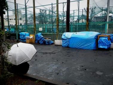 Minami Senju: A homeless man sits alone as a cold and dreary rain falls about him.