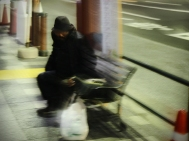 Asakusa: A homeless man prepares for a night on a bus bench.