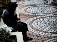Shinjuku: A homeless man sits amidst a bustling city.