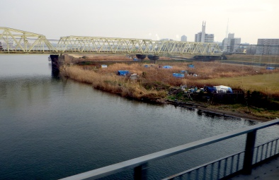 Blue tarp tents along the Edo River.